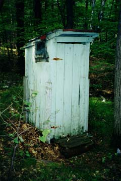The old outhouse with the door closed