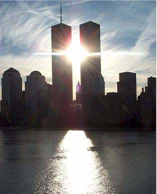 This picture was taken by a lady returning on a cruise this past summer. SHE Writes: As I watched the beautiful skyline of New York City float past me I noticed the sun was about to line up just behind the twin towers. I was lucky enough to snap the picture at exactly the right moment. If you look at the sun rays it is almost prophetic - a little spooky.